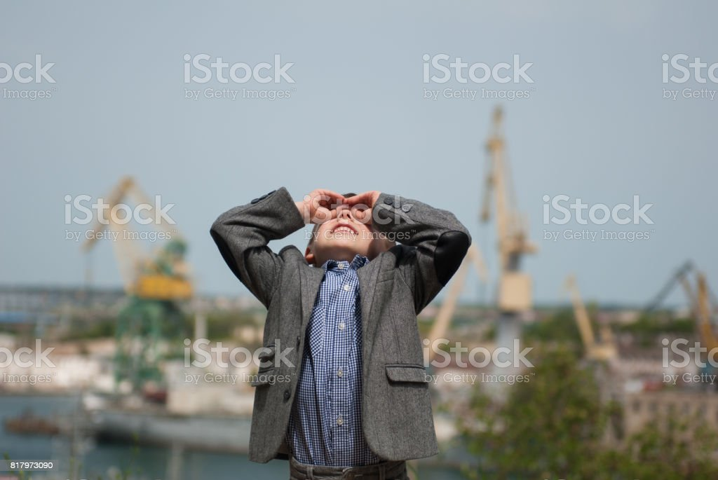 smiling little boy looking up with his hands in the form of binoculars stock photo