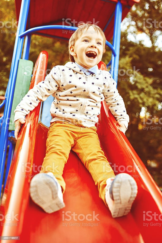 A smiling little boy on a slide stock photo