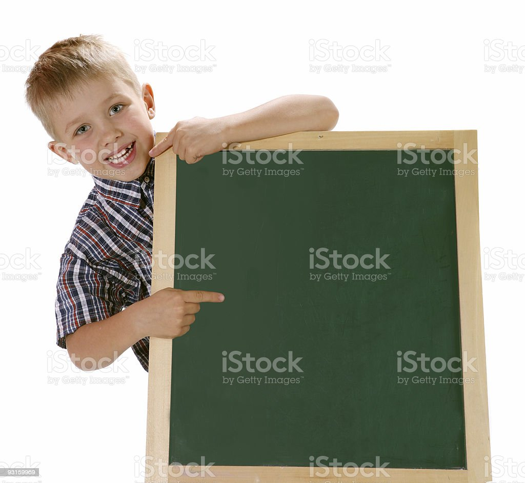 Smiling little boy pointing a sign at the school blackboard.. royalty-free stock photo