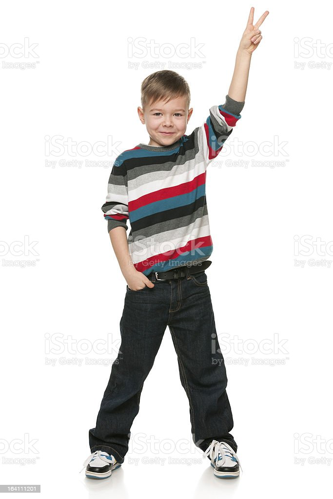 Smiling little boy shows victory sign royalty-free stock photo
