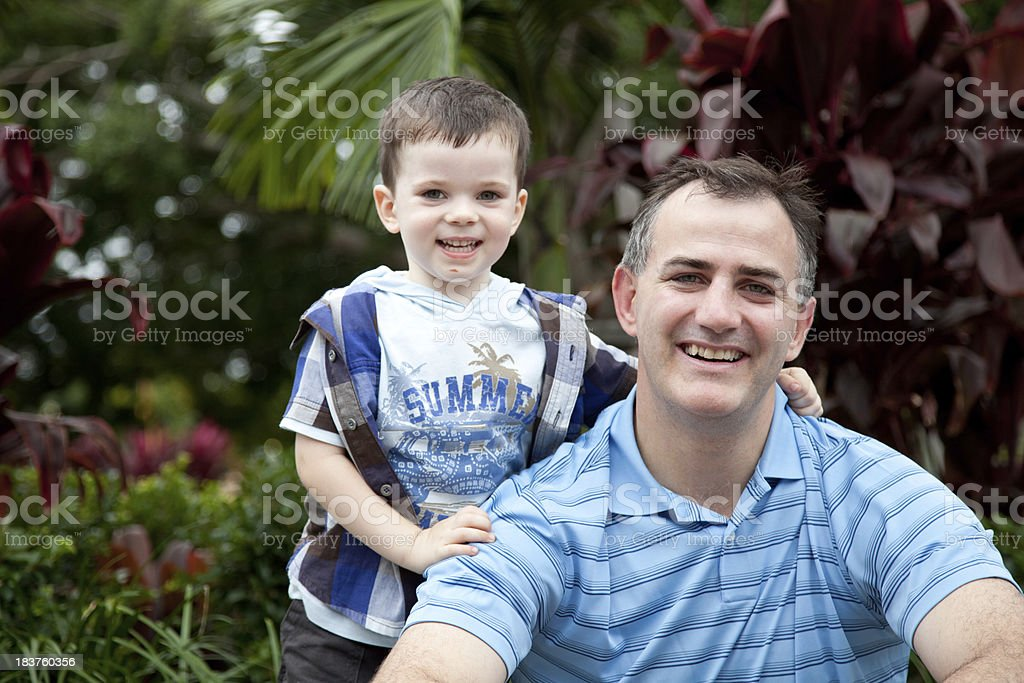 Smiling Little boy son with arm around Father outdoors royalty-free stock photo