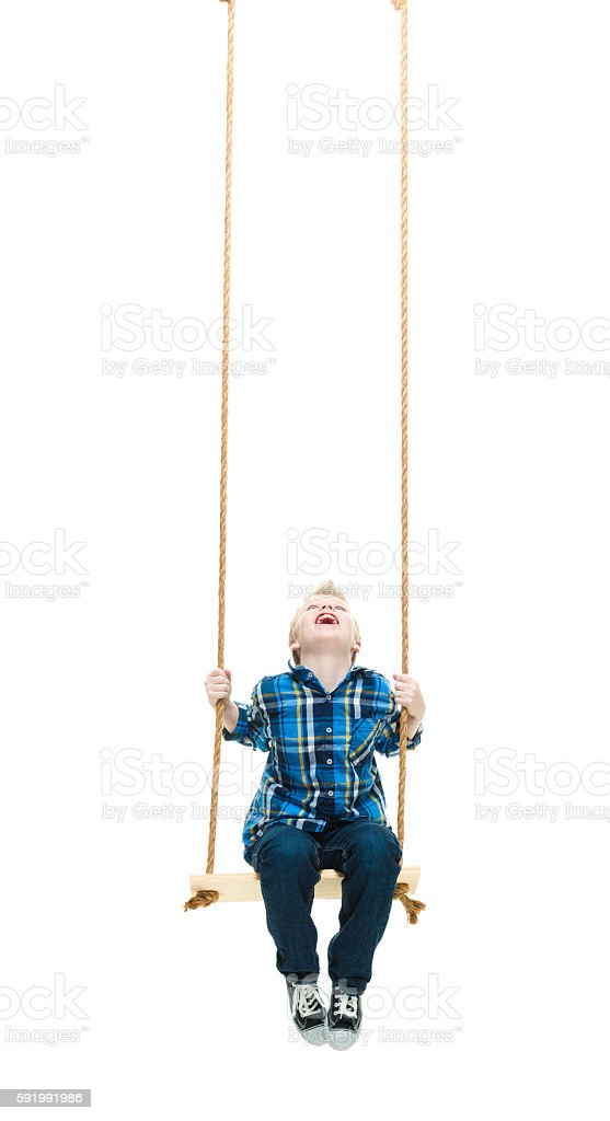 Smiling little boy swinging stock photo