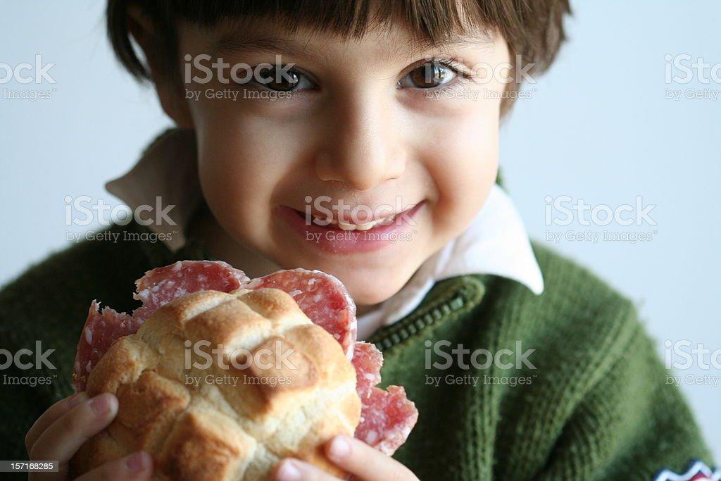 Smiling Little Boy Toddler Eating Salami Sandwich on Bun royalty-free stock photo