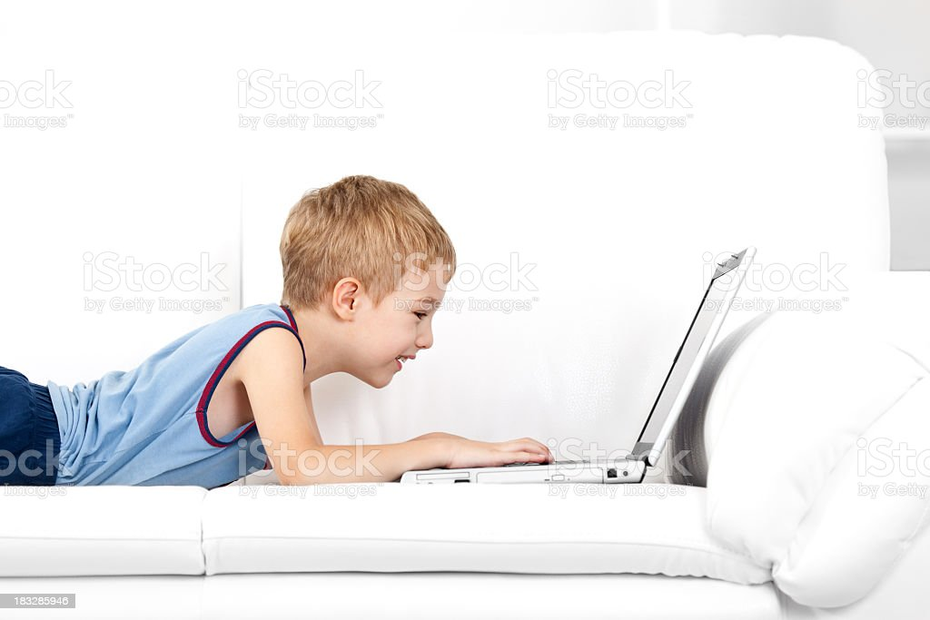 Smiling little boy typing on laptop computer in domestic room royalty-free stock photo