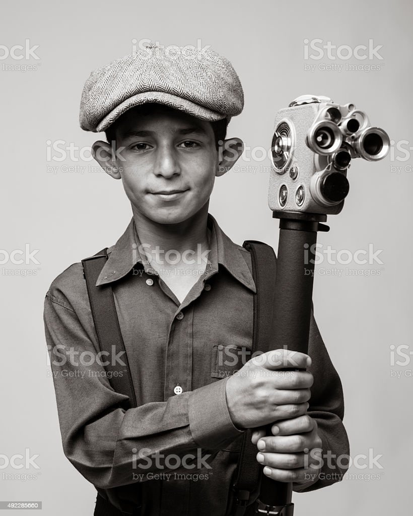 Smiling little boy wearing newsboy cap and holding camera stock photo