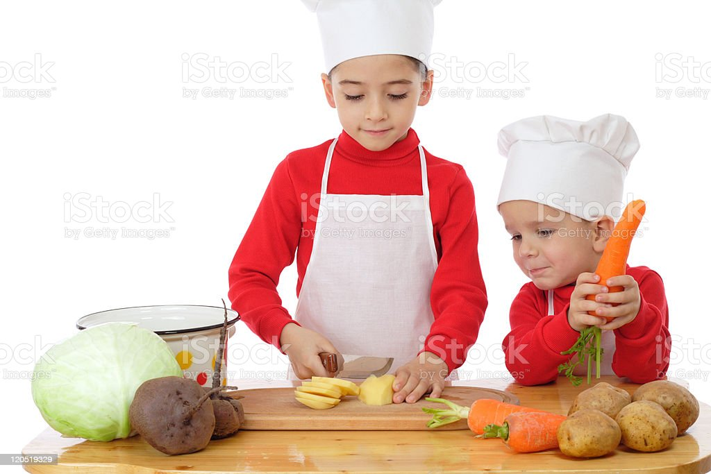 Smiling little chief-cookers on the desk with vegetables royalty-free stock photo