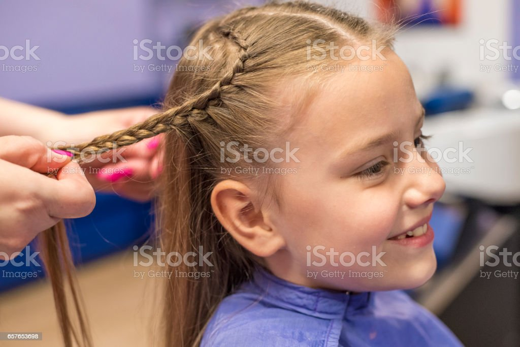 Smiling little girl at the hairdresser stock photo
