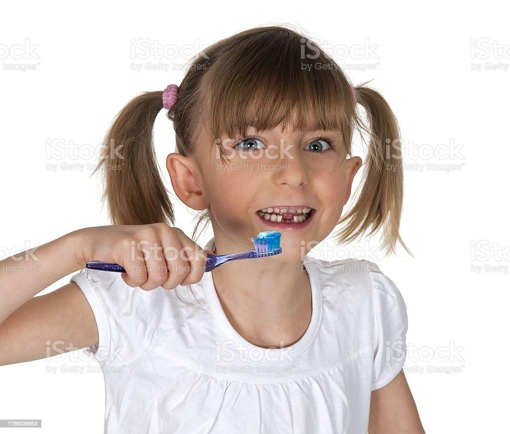 smiling little girl brushing teeth stock photo