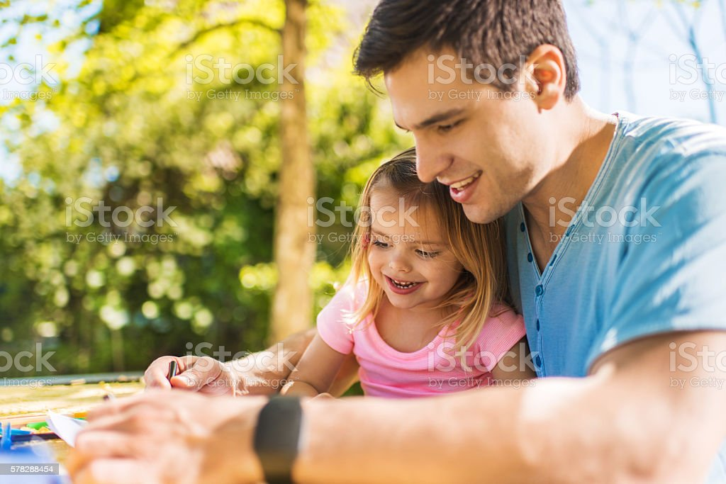 Smiling little girl drawing in the backyard with her father. stock photo