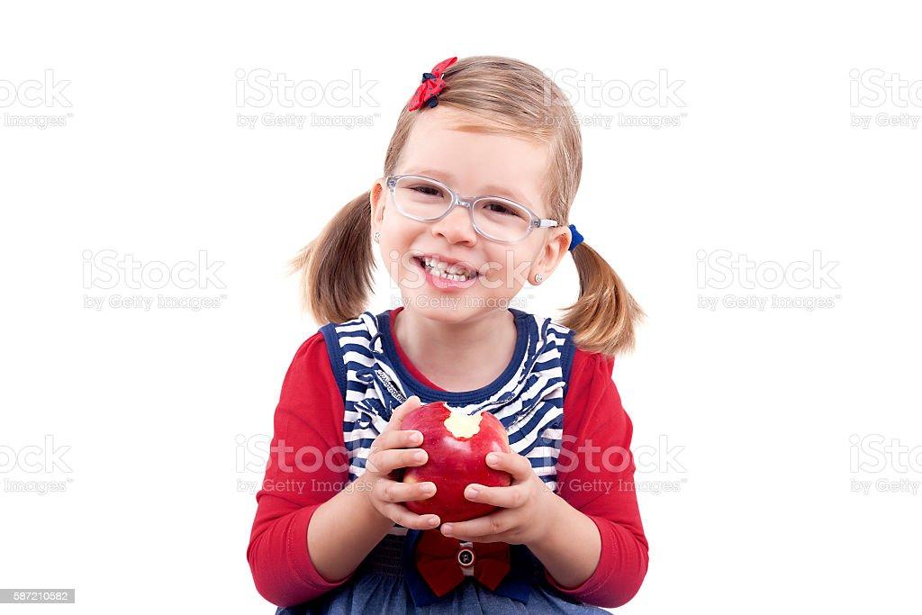Smiling little girl eating a red apple photo libre de droits
