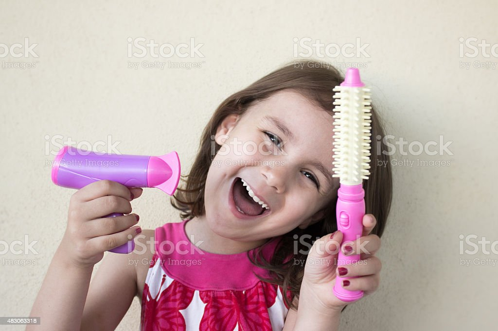 Smiling little girl holding hair dryer and comb stock photo
