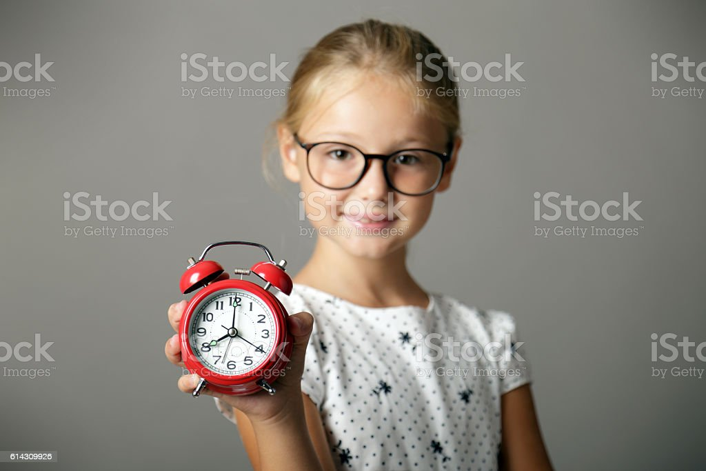Smiling little girl holds an alarm clock in hand stock photo