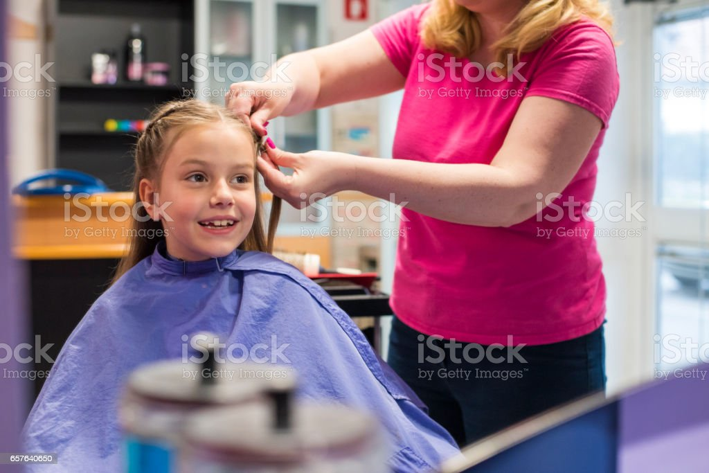 Smiling little girl in a hairdressing salon stock photo