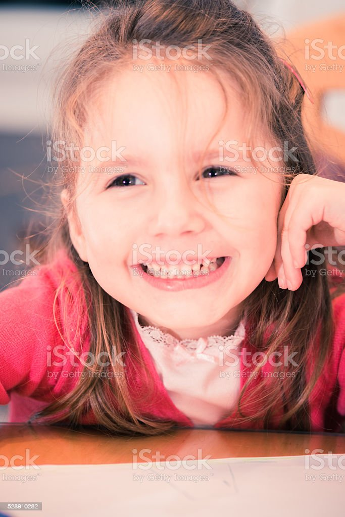 Smiling Little Girl in Pink While Drawing at Home, Europe stock photo