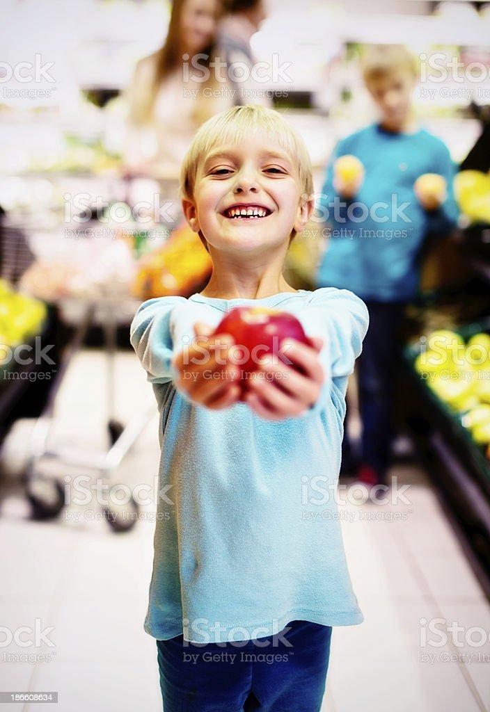 Smiling little girl in supermarket chooses apple for teacher royalty-free stock photo