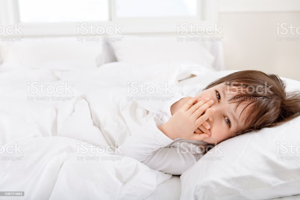 Smiling little girl laying in bed royalty-free stock photo