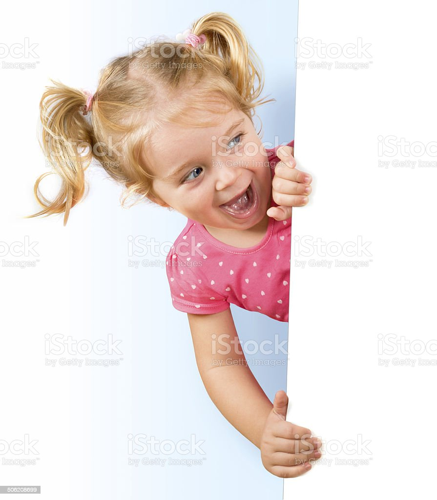 Smiling little girl looking behind a white board stock photo