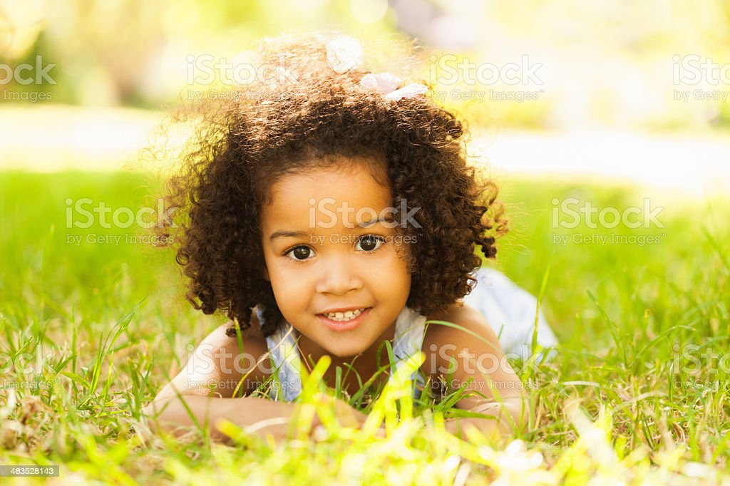 Smiling Little Girl Lying On Grass royalty-free stock photo