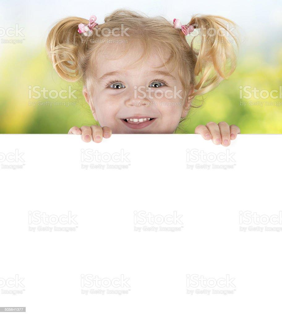 Smiling little girl peeking behind a board stock photo