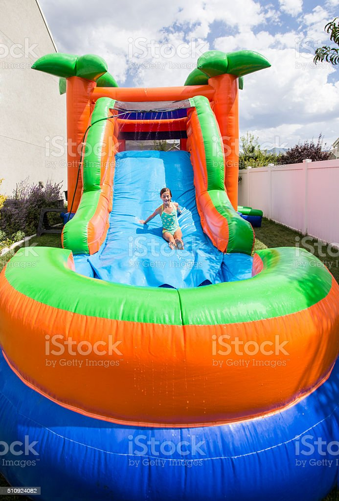 Smiling little girl playing on inflatable slide bounce house outdoors stock photo