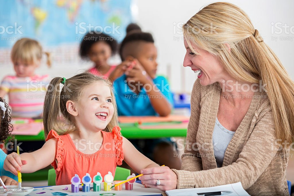 Smiling little girl playing with paints at daycare with teacher stock photo