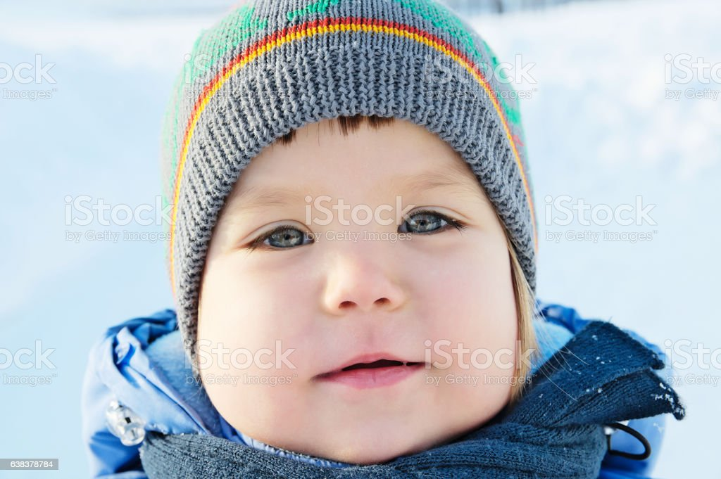 Smiling little girl portrait at winter in warm clothes stock photo