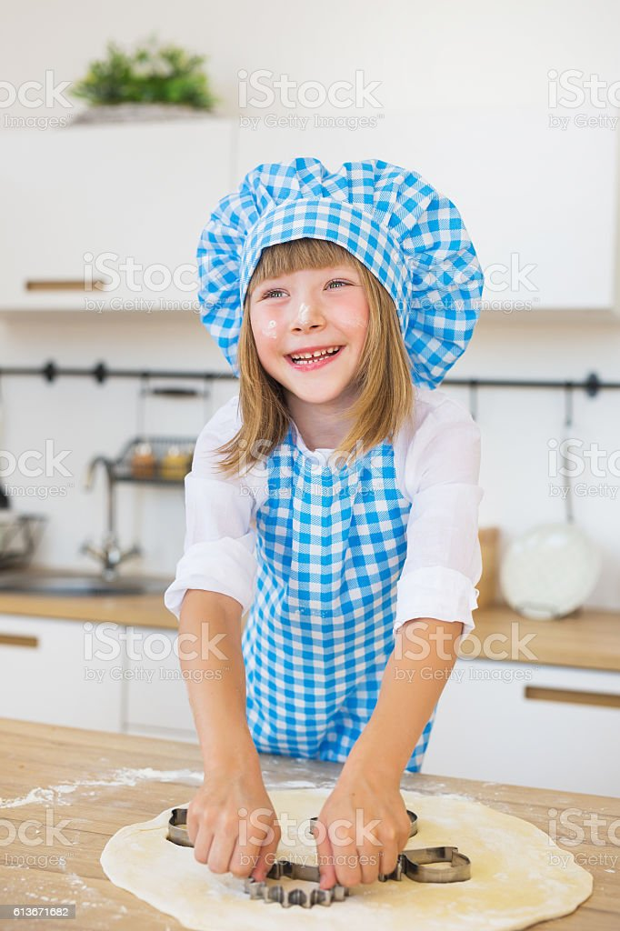Smiling little girl pushes by a cake tin stock photo
