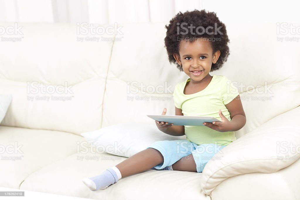 Smiling little girl using tablet pc. royalty-free stock photo