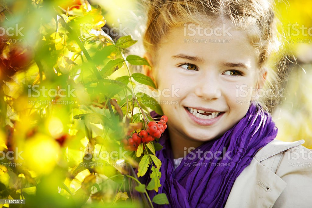 Smiling Little Girl Wearing Coat and Purple Scarf royalty-free stock photo