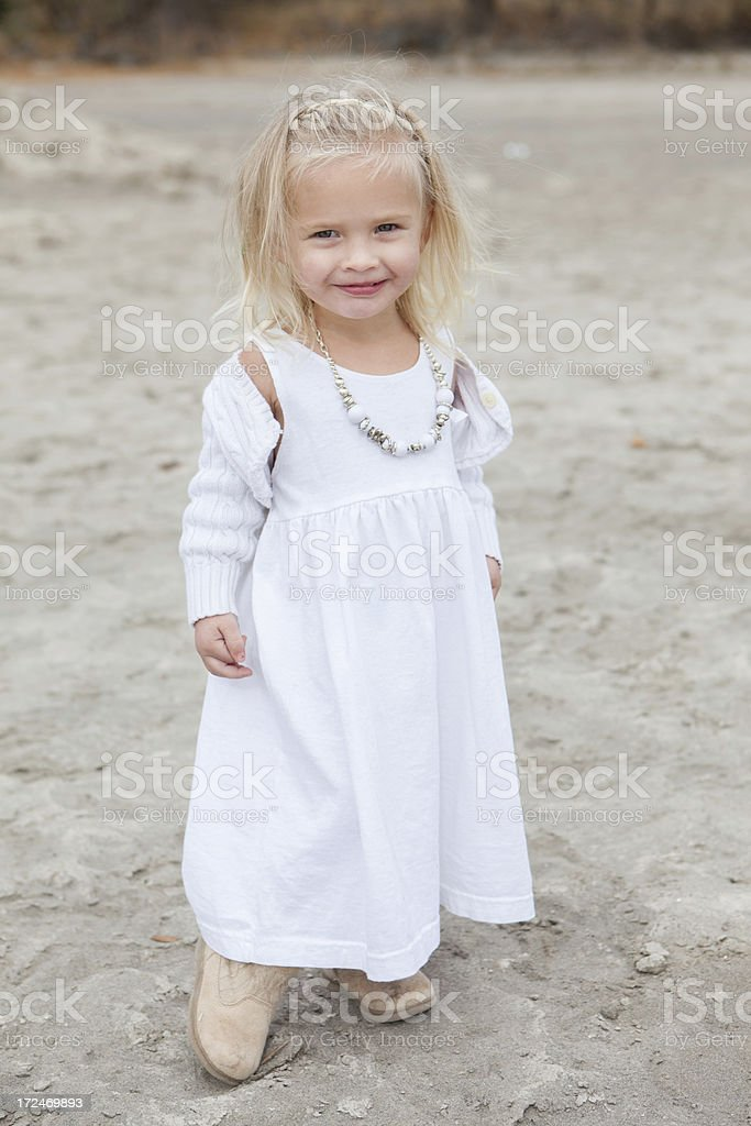 Smiling Little Girl Wearing White and Wind Blowing Her Hair royalty-free stock photo