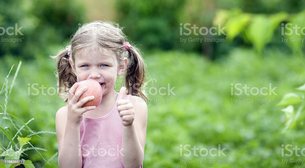 Smiling Little girl with a Apple. royalty-free stock photo