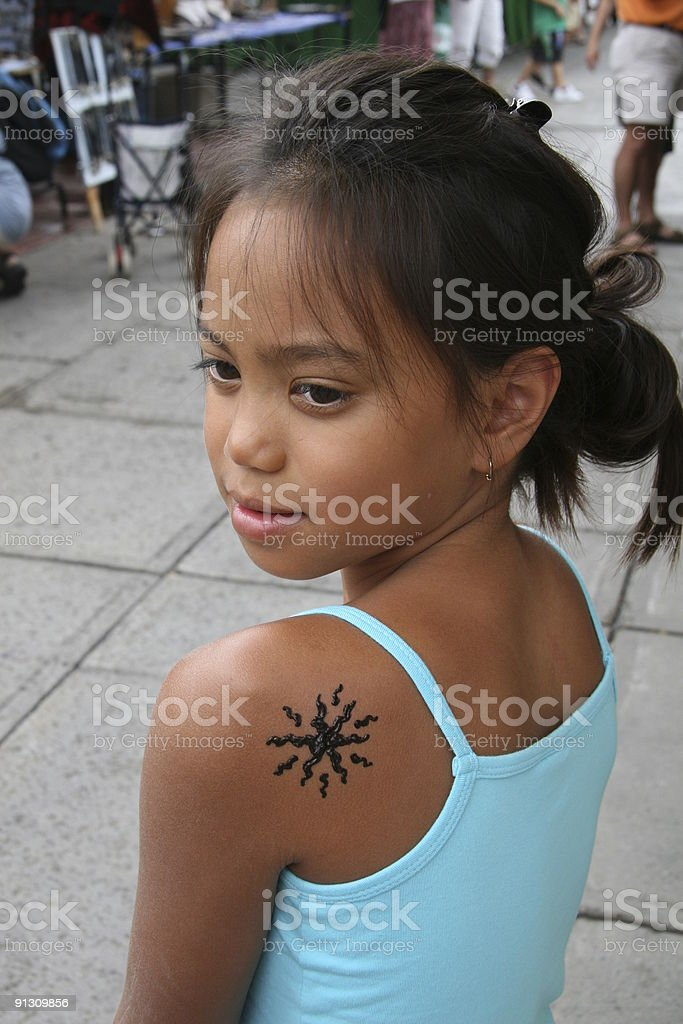 Smiling little girl with a temporary Henna tattoo stock photo