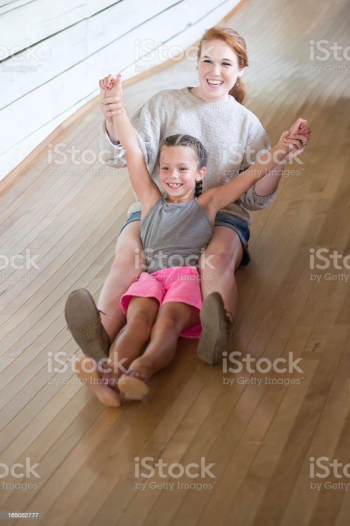 Smiling Little Girl with Baby Sitter Sliding Down Large Slide stock photo