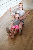 Smiling Little Girl with Baby Sitter Sliding Down Large Slide