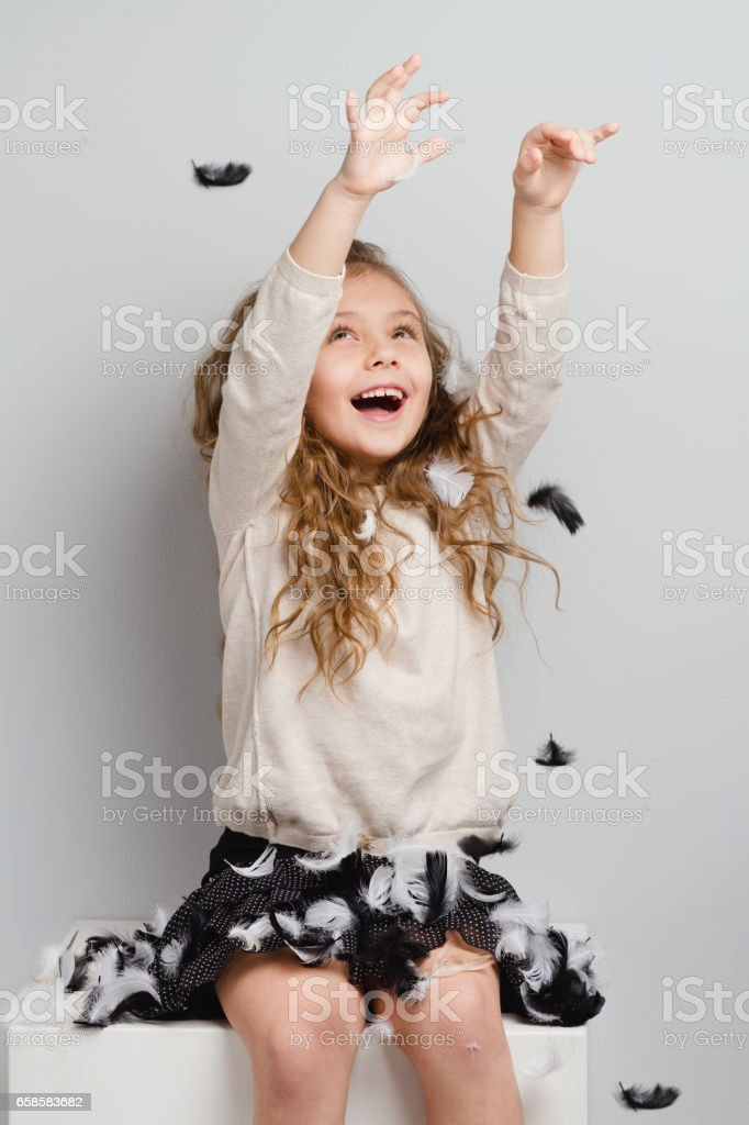 Smiling little girl with feathers. stock photo