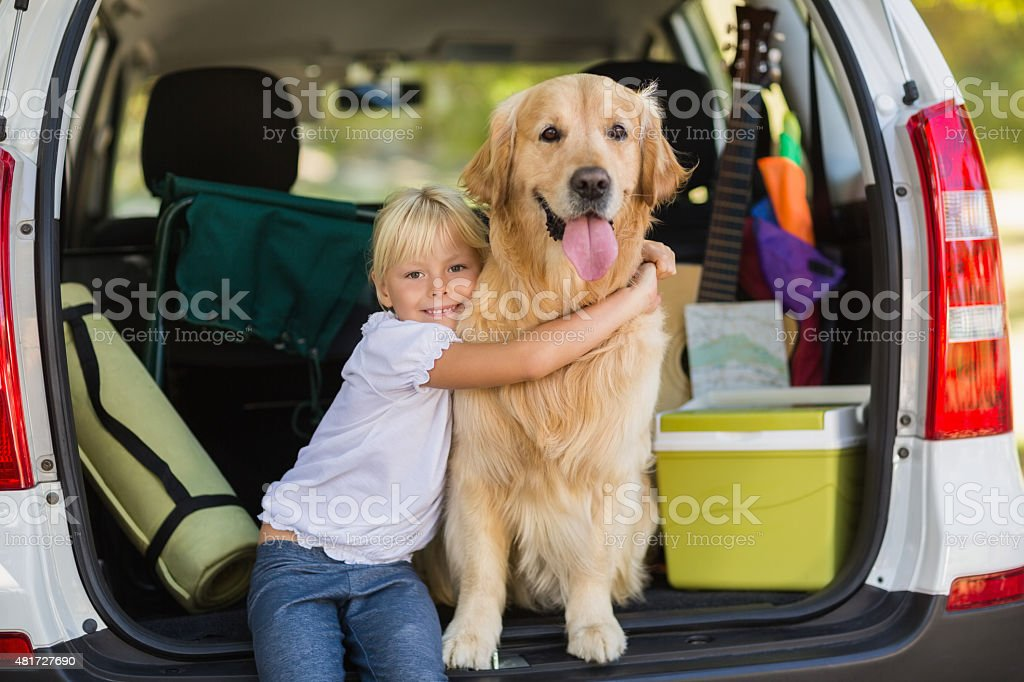 Smiling little girl with her dog in car trunk stock photo