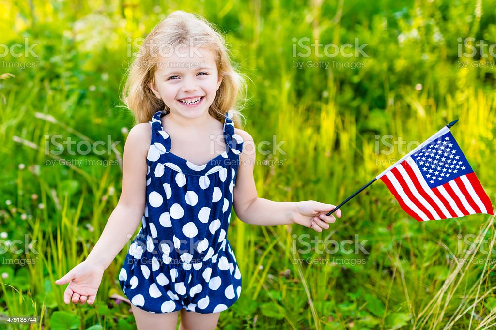 Smiling little girl with long curly hair holding american flag stock photo