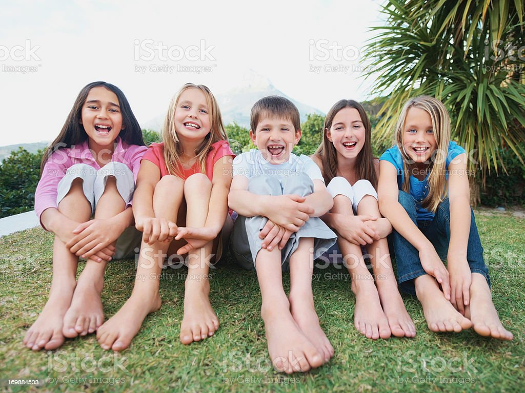 Smiling little kids sitting in a line on grass stock photo