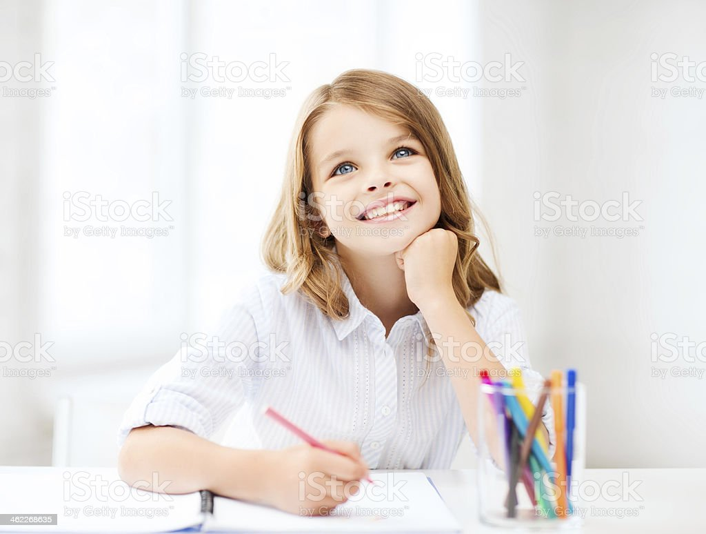 smiling little student girl drawing at school stock photo