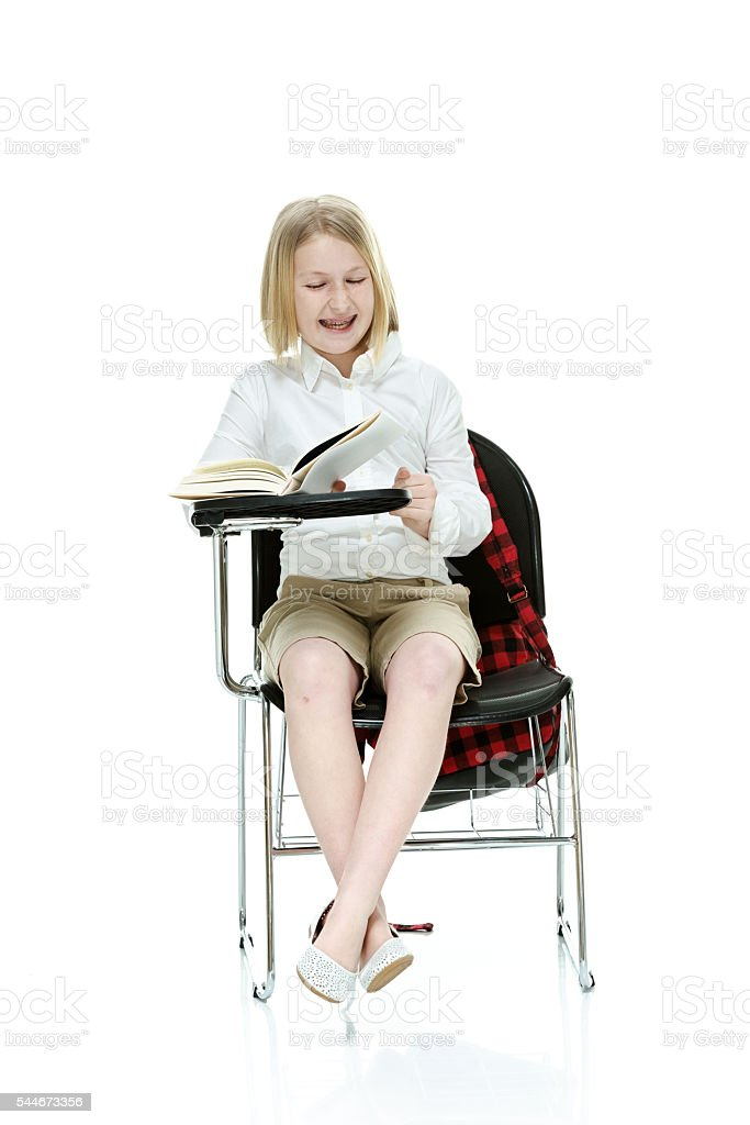 Smiling little student reading book stock photo