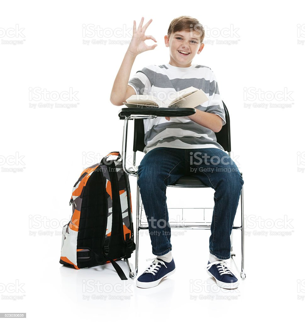 Smiling little student showing ok sign stock photo