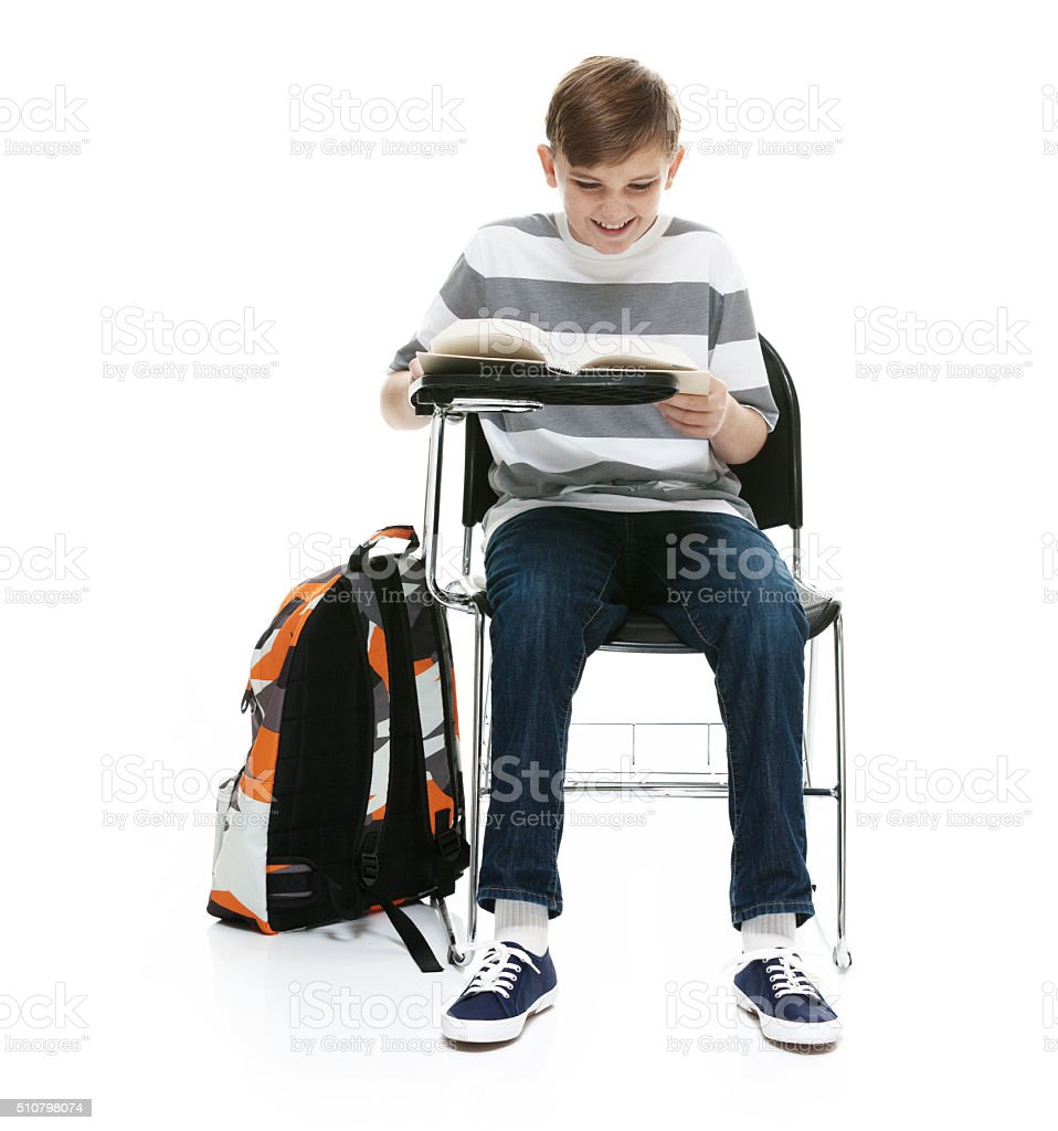 Smiling little student sitting and reading book stock photo
