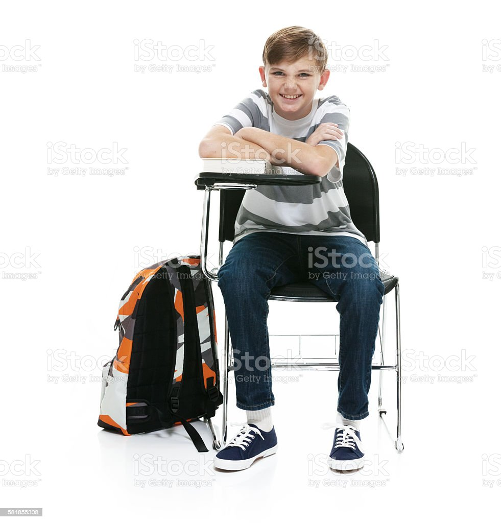Smiling little student sitting on chair stock photo