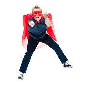 Smiling little superhero jumping