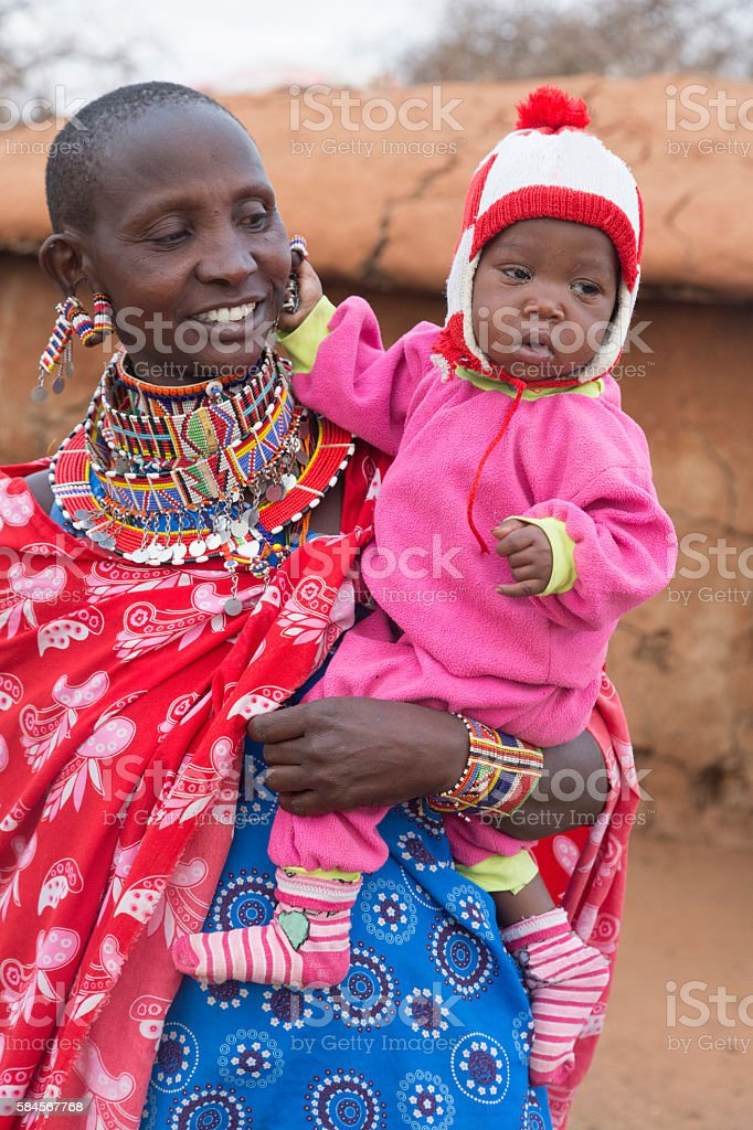 Smiling Maasai mother with young daughter outside hut, Kenya stock photo