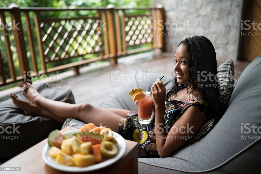 Smiling Malaysian woman enjoying in a cocktail on a terrace. stock photo