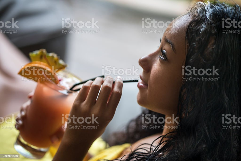 Smiling Malaysian woman enjoying in a fruit cocktail. stock photo