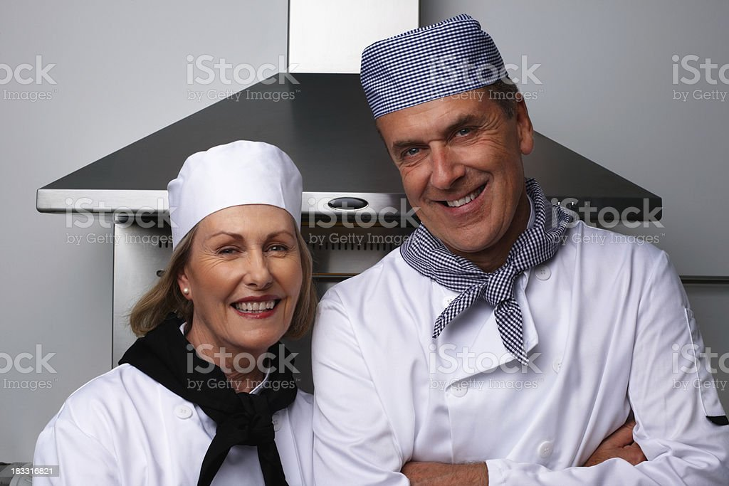 Smiling male and female chefs together standing in the kitchen royalty-free stock photo