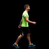 Smiling male athlete walking
