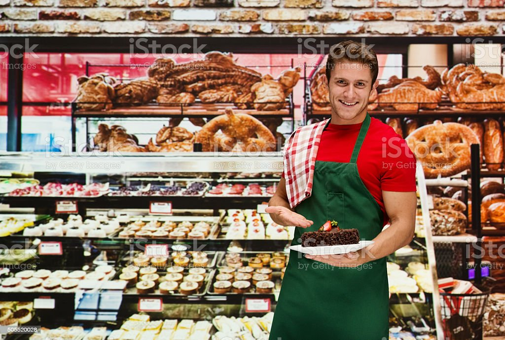 Smiling male baker presenting with cake in bakery stock photo